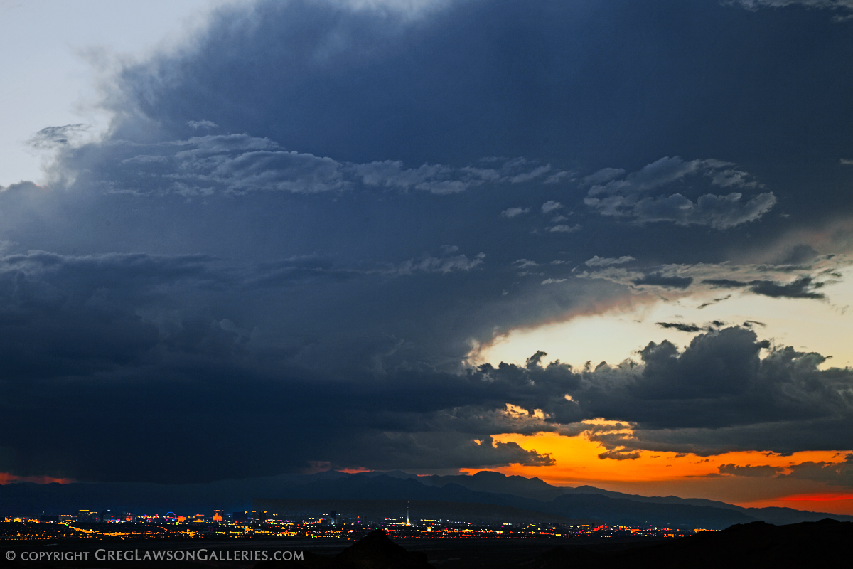 Evening storm towers above Nevada's Spring Mountain National Recreation Area as the Las Vegas Strip comes to life. Greg Lawson Photography.